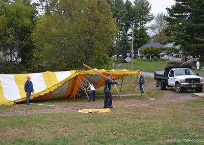 Brothers MICM raise the tent for annual fall bazaar fundraiser.