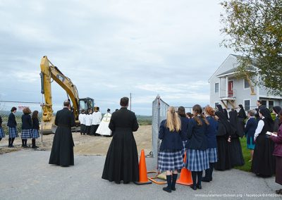 Students and faculty of IHM School pray at the site of the building.