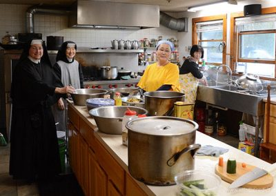 Sisters and volunteers make Korean food for fundraising event.
