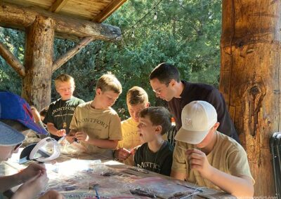 Brother Patrick helps campers make Rosaries